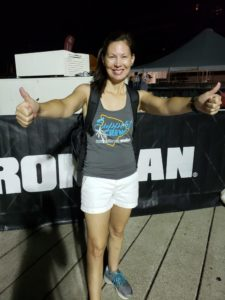 Kathleen standing in front of the Ironman banner on race morning