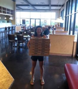 photo of pizza delivery. Camp coach bringing triathlon camp athletes lots of pizza.